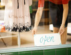 woman placing open sign in store window