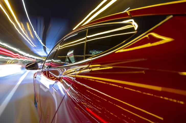 red car on highway with streaking lights